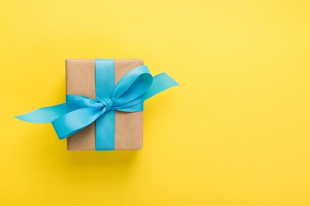 Geschenk verpakt en gedecoreerd met blauwe strik op geel met copyspace. plat leggen, bovenaanzicht