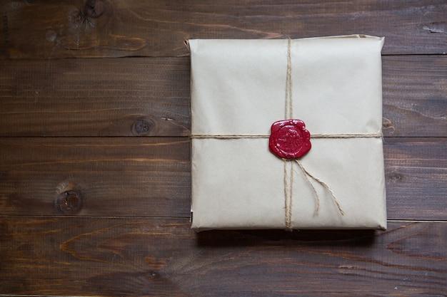 Geschenk verpakt in kraftpapier, gebonden met touw en gelijmde lakzegel. liggend op de tafel met plaats voor tekst