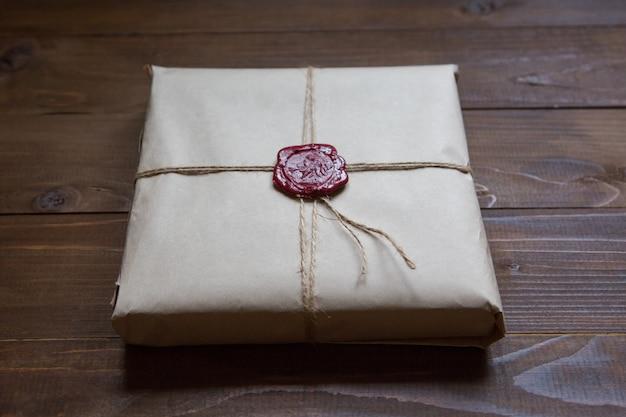 Geschenk verpakt in kraftpapier, gebonden met touw en gelijmde lakzegel. liggend op de tafel. tweede kerstdag