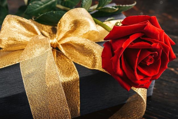 Geschenk verpakt in zwart papier en een gouden lint. bovenop de doos staat een luxe rode roos.