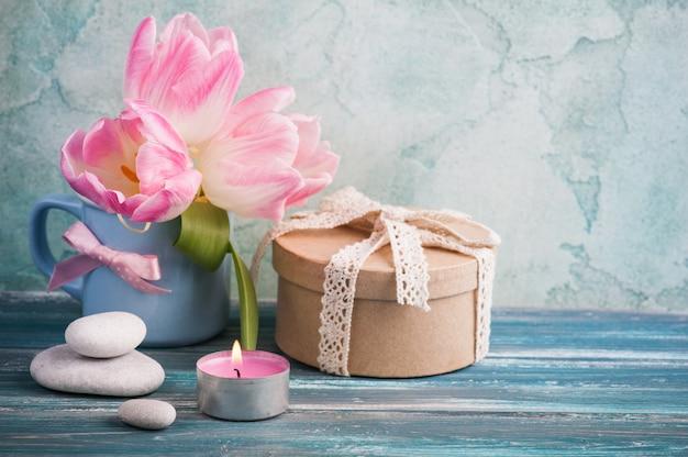 Geschenkdoos, aangestoken kaars en tulpen