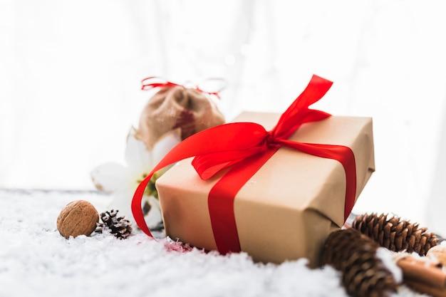 Geschenkdoos dichtbij bloem en winkelhaken tussen decoratieve sneeuw