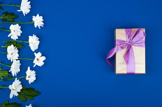 Geschenkdoos en bloemen op blauwe tafel. wenskaart voor verjaardag, dames of moederdag. bovenaanzicht