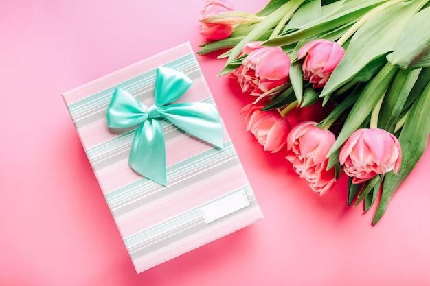 Geschenkdoos en boeket van prachtige tulpen op roze