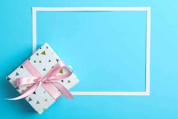 Geschenkdoos en frame op kleur, ruimte voor tekst. bovenaanzicht