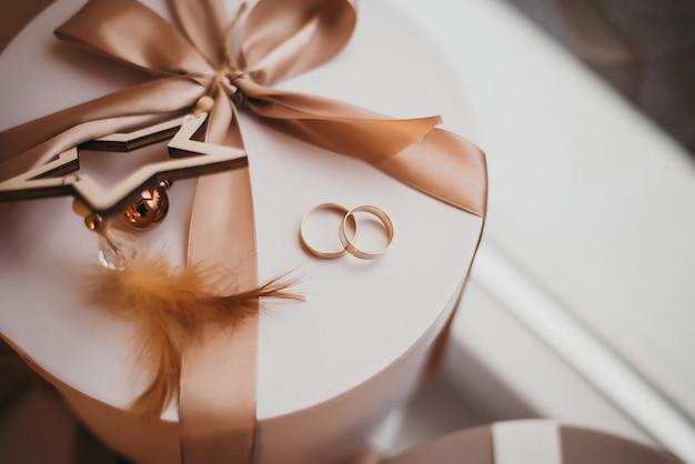 Geschenkdoos en gouden verlovingsring met diamant op roze pastelachtergrond
