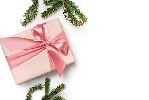 Geschenkdoos en kerstboomtakken op wit wordt geïsoleerd.