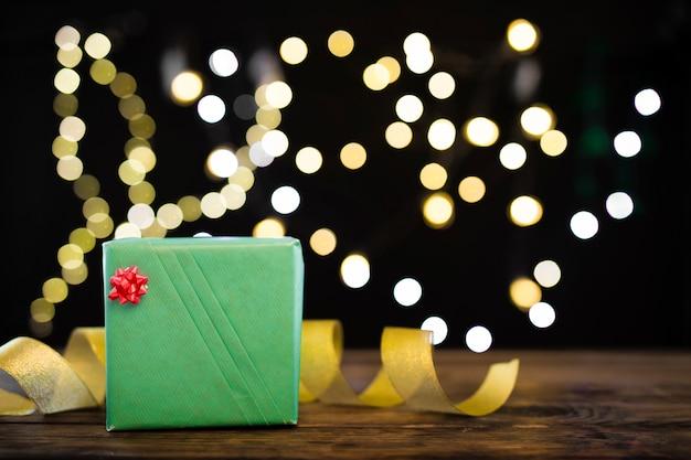 Geschenkdoos en lint in de buurt van garland lichten