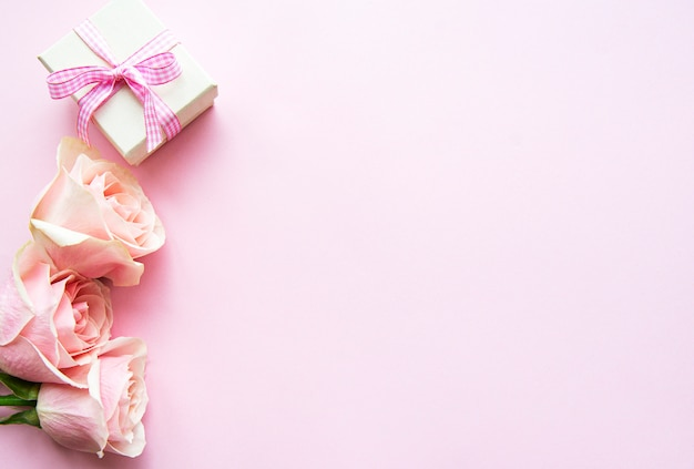 Geschenkdoos en roze rozen op een pastel roze achtergrond