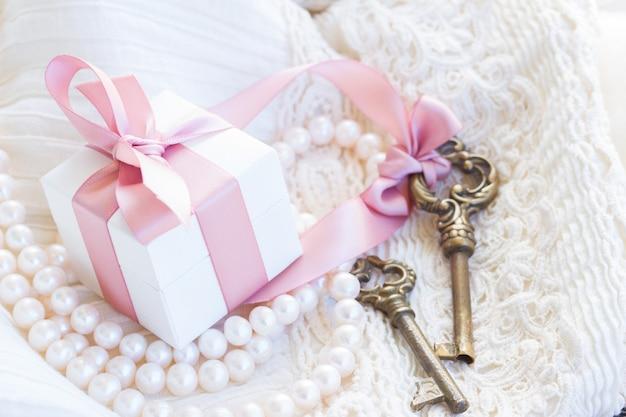 Geschenkdoos en sleutels met parelsieraden en kant