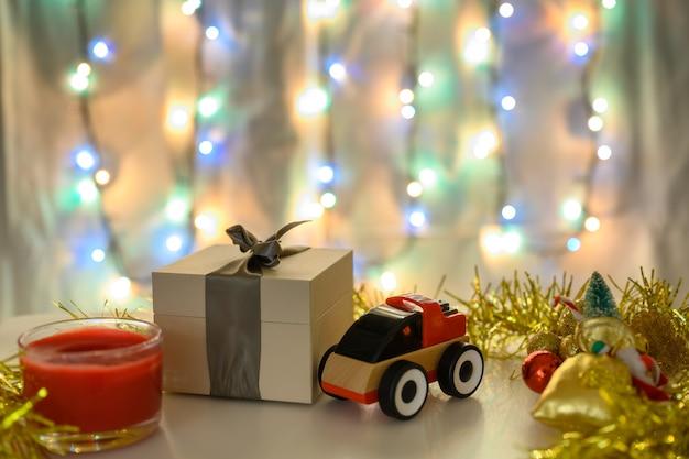 Geschenkdoos en speelgoedauto op een kerstachtergrond met een gloeiende slinger in koude kleuren.