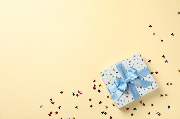 Geschenkdoos en ster glitter op kleur achtergrond, bovenaanzicht