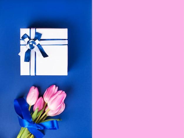 Geschenkdoos en tulpen op roze en klassiek blauw