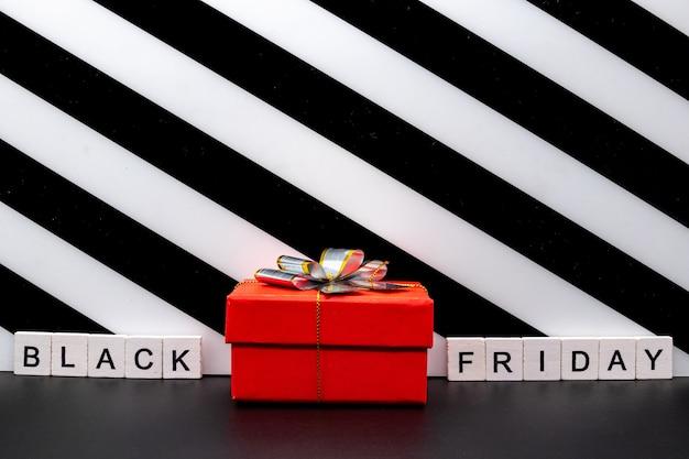 Geschenkdoos en zwarte vrijdag tekst op papier scheur
