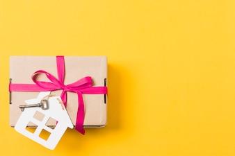 Geschenkdoos gebonden met sleutel en huis-model op heldere gele achtergrond