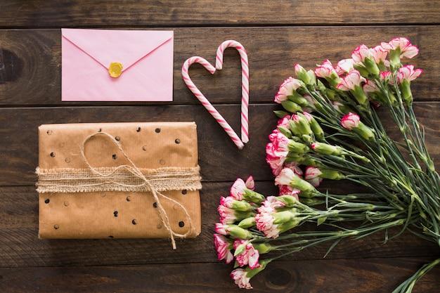 Geschenkdoos in de buurt van boeket bloemen, envelop en snoep stokken