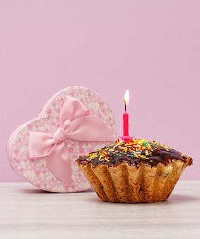 Geschenkdoos in de vorm van een hart en smakelijke verjaardagsmuffin met chocoladeglazuur en karamel, versierd met brandende feestelijke kaars op lila achtergrond. gelukkige verjaardag minimaal concept.