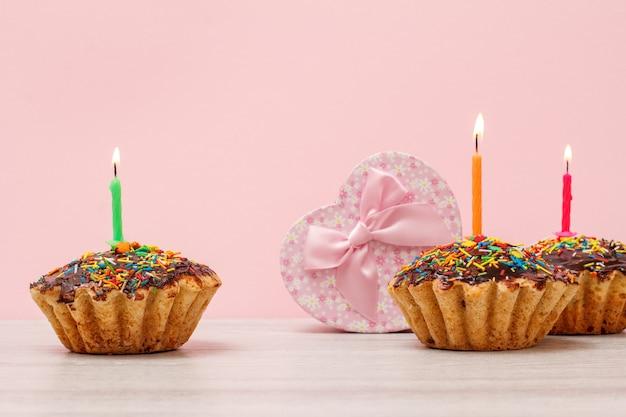 Geschenkdoos in de vorm van een hart en smakelijke verjaardagsmuffins met chocoladeglazuur en karamel, versierd met brandende feestelijke kaars op houten en roze achtergrond met kopie ruimte... gelukkige verjaardag concept.
