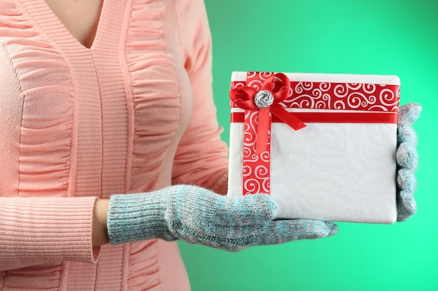 Geschenkdoos in vrouwelijke hand op kleuroppervlak