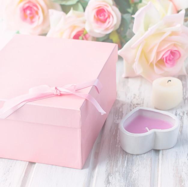 Geschenkdoos, kaars en een boeket rozen
