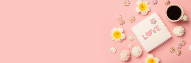 Geschenkdoos, kopje koffie, bloemen, schuimgebakjes en snoep op een roze ondergrond