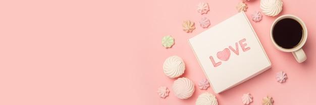 Geschenkdoos, kopje koffie en schuimgebak op een roze ondergrond