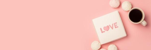 Geschenkdoos, kopje koffie, meringue en snoep op een roze ondergrond