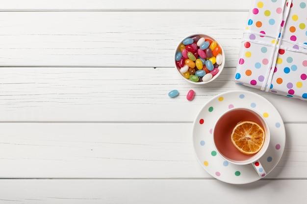 Geschenkdoos, kopje thee en kleurrijke snoepjes op witte houten achtergrond