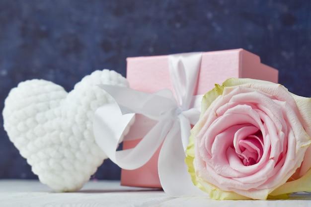 Geschenkdoos met bloemen en wit pluche gebreid hart op roze achtergrond.