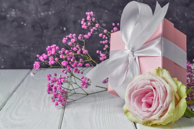 Geschenkdoos met bloemen op roze valentijnsdag achtergrond.