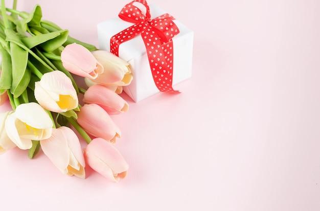 Geschenkdoos met boeket tulpen op roze achtergrond. lente of vakantie concept, 8 maart, internationale vrouwendag, verjaardag.