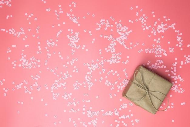 Geschenkdoos met bruin kraftpapier omgeven met roze madeliefjes en flatlay roze achtergrond, lente