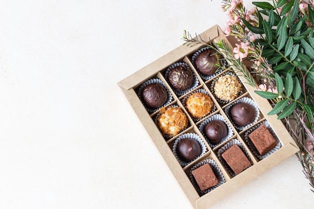 Geschenkdoos met diverse soorten chocolaatjes en roze bloemen