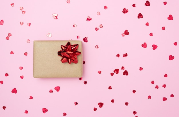 Geschenkdoos met een rode strik aan de zijkant op een roze achtergrond. vrije ruimte voor tekst. feestdagen, kerstmis, valentijnsdag.