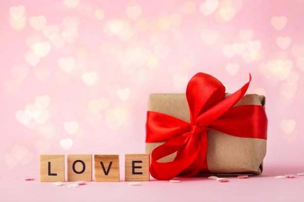 Geschenkdoos met een rode strik en het woord liefde gemaakt van houten letters op een roze achtergrond met bokeh