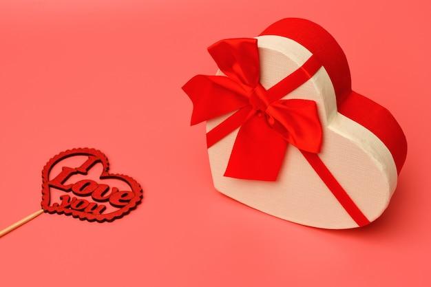 Geschenkdoos met een rood lint hartvormig op een roze achtergrond. valentijnsdag