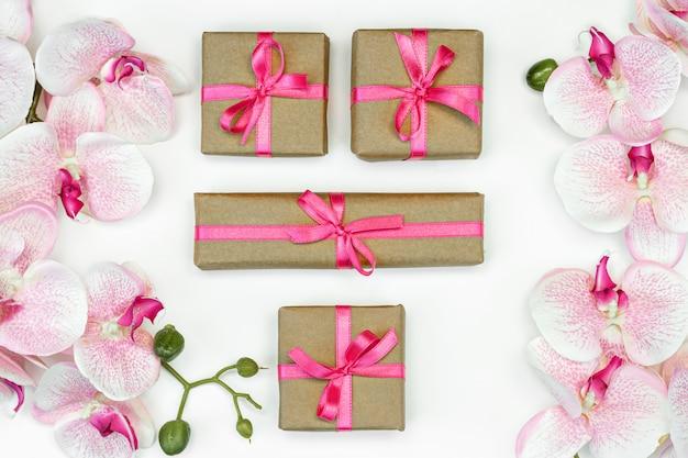 Geschenkdoos met een roze lint en orchideebloemen