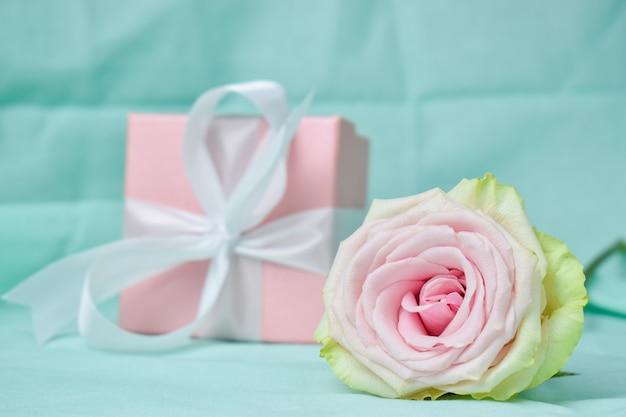 Geschenkdoos met een roze roos op een licht turkooizen achtergrond. v.