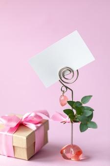 Geschenkdoos met een roze strik en een blanco kaart.