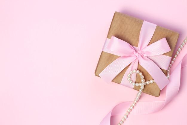 Geschenkdoos met een roze strik en parel kralen op een pastel roze achtergrond. plat lag stijl.