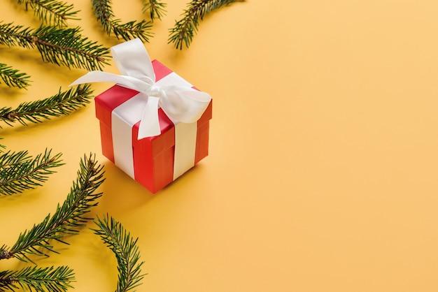 Geschenkdoos met een strik tussen de kerstboomtakken op een gele