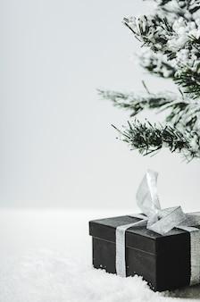 Geschenkdoos met een strik van zilver lint onder de spar.