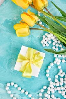 Geschenkdoos met geel lint in de buurt van tulpenbloemen en ketting