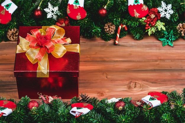 Geschenkdoos met gouden kleur lint op hout achtergrond met kerstboom en traditionele ornamenten xmas rekwisieten met kopie ruimte. concept van gelukkig en vreugdevol in festival.