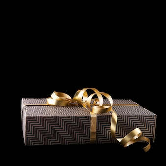 Geschenkdoos met gouden lint in minimalistische stijl geïsoleerd op donkere achtergrond
