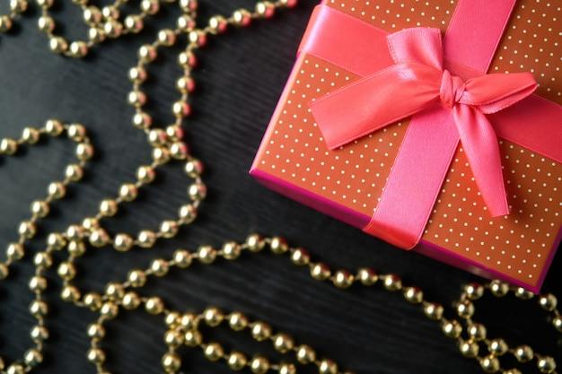 Geschenkdoos met gouden slinger op houten achtergrond