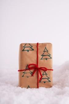 Geschenkdoos met kerstbomen patroon en een rood lint in de sneeuw