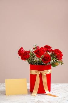 Geschenkdoos met mooie bloemen en blanco kaart op tafel tegen een achtergrond met kleur