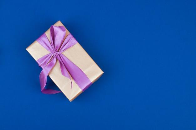 Geschenkdoos met paars lint geïsoleerd op blauwe ruimte. bovenaanzicht