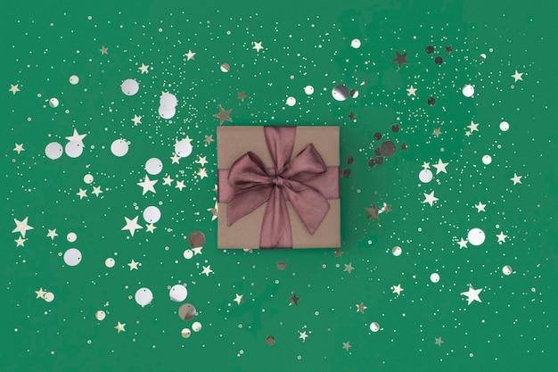 Geschenkdoos met paarse strik op groene achtergrond met confetti geschenkdoos met paarse strik op groene achtergrond met confetti